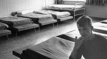 A young boy sits on a dormitory bed in 1971 the institution most recently known as the Huronia Regional Centre. (Morton Shulman/Ontario Ministry of Community and Social Services/Morton Shulman/Ontario Ministry of Community and Social Services)