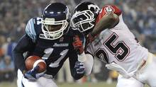 Toronto Argonauts receiver Dontrelle Inman blocks a tackle from Calgary Stampeders defender Keon Raymond  during  the CFL's 100th Grey Cup game between the Toronto Argonauts and the Calgary Stampeders at the Rogers Centre on Nov 25 2012. (Fred Lum/The Globe and Mail)