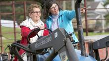 Ontario Premier Kathleen Wynne drives a tractor with instruction from farmer Sandra Vos, right, at a campaign event in Paris, Ontario on Tuesday May 20, 2014, 2014. (Frank Gunn/THE CANADIAN PRESS)