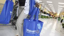 A shopper carries her purchases from a Walmart in Chicago. (JIM YOUNG/REUTERS)