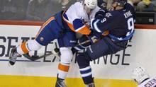 New York Islanders' Thomas Hickey (L) checks Winnipeg Jets' Evander Kane during the third period of their NHL hockey game in Winnipeg April 20, 2013. (FRED GREENSLADE/REUTERS)