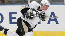 Pittsburgh Penguins' Sidney Crosby (87) follows through on a shot during the third period of an NHL hockey game against the New York Rangers at Madison Square Garden in New York, Monday, Nov. 29, 2010. The Penguins won 3-1. (Paul J. Bereswill)