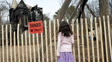 A child looks at the charred Jamie Bell Adventure Playground in Toronto's High Park that was suspected to have been deliberately set ablaze early Saturday morning. (Michelle Siu/The Globe and Mail/Michelle Siu/The Globe and Mail)