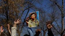 A supporter raises the portrait of former Pakistani president Pervez Musharraf as he and others chant slogans outside a court in Islamabad Feb. 18, 2014. (Anjum Naveed/Associated Press)