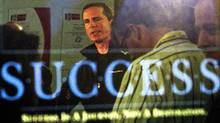 Ontario Liberal Leader Dalton McGuinty is reflected in a poster as he takes questions from reporters at a campaign stop in Vaughan on Oct. 3, 2011. (Frank Gunn/THE CANADIAN PRESS)
