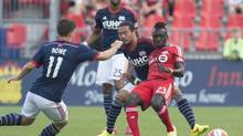 Toronto FC's Dominic Oduro, right, battles for the ball with New England Revolution's, from left to right, Kelyn Rowe, Darrius Barnes, and Daigo Kobayashi during the first half of MLS soccer action at BMO Field (DARREN CALABRESE/THE CANADIAN PRESS)