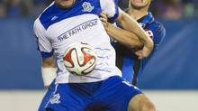Montreal Impact's Karl Ouimette and FC Edmonton's Frank Jonke battle for the ball (Graham Hughes/THE CANADIAN PRESS)