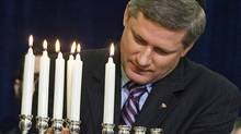 Prime Minister Stephen Harper takes part in a menorah lighting ceremony on Parliament Hill on December 19, 2006. (FRED CHARTRAND)