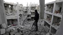 A Free Syrian Army fighter stands in front of a building destroyed by Syrian Army air strikes in Damascus onThursday. (GORAN TOMASEVIC/REUTERS)