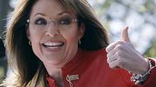 Sarah Palin flashes a thumbs up towards her husband Todd before a speech in Boston last year. (AP)