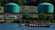 Members of the Squamish and Tsleil-Waututh First Nations paddle canoes on the waters of Burrard Inlet near the Kinder Morgan Burnaby Terminal for a ceremony to show opposition to the proposed expansion of the Trans Mountain pipeline, in North Vancouver, B.C., on Sept. 1, 2012. (Darryl Dyck/The Canadian Press)