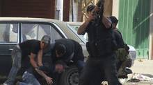 A Sunni Muslim gunman fires his rifle as others help an injured colleague during clashes at the Sunni Muslim Bab al-Tebbaneh neighbourhood in Tripoli, northern Lebanon, May 14, 2012. (Reuters/REUTERS)
