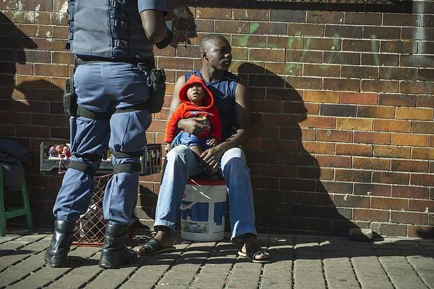A man holds a child while a police officer check his identity in Hilbrow Johannesburg, an area mostly inhabited by foreign nationals, on April 27, 2015. South Africa has conducted heavy-handed raids on businesses to search for foreign workers.