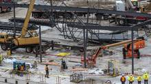 A tarp covers a body where police say a man died after being trapped in a partial collapse at a construction site at a the Sheridan Centre shopping mall in Mississauga, Monday January 13, 2014.
