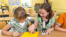 Two elementary students work with a microscope. (Thinkstock/Thinkstock)