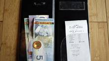 A bill is paid in cash at an Ottawa restaurant. (Blair Gable/Blair Gable for The Globe and Mail)