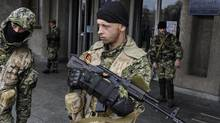 Armed pro-Russian activists stand outside the Ukrainian regional administration building which they seized in the eastern Ukrainian town of Slovyansk on April 14, 2014. (EVGENIY MALOLETKA/ASSOCIATED PRESS)