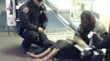 New York police officer Larry DePrimo gives a homeless man a pair of boots and socks in Times Square in this November 14, 2012 handout photo courtesy of Jennifer Foster. (Jennifer Foster/Reuters)