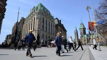 Pedestrians cross Elgin Street in view of the Peace Tower on Parliament Hill. (Sean Kilpatrick/Canadian Press)