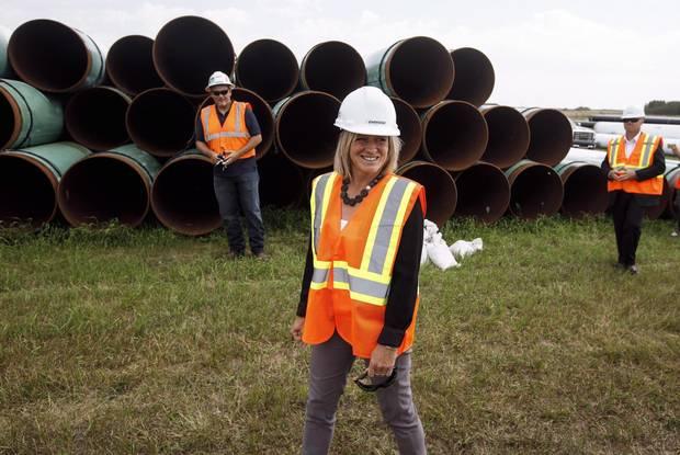 Alberta Premier Rachel Notley, walking past lengths of pipe in Hardisty, Alta., in August, 2017.