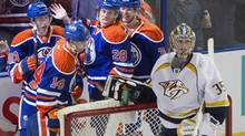 Nashville Predators goalie Pekka Rinne (35) looks on as Edmonton Oilers' Ryan Nugent-Hopkins (93), Jordan Eberle (14), Ryan Jones (28) and Philip Larsen (36) celebrate a goal during second period NHL action in Edmonton, Alta., on Tuesday March 18, 2014. (JASON FRANSON/THE CANADIAN PRESS)