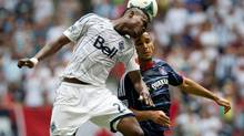 Vancouver Whitecaps' Gershon Koffie, left, of Ghana, and Chicago Fire's Alex Monteiro de Lima vie for the ball during the first half of an MLS game in Vancouver, B.C., on Sunday July 14, 2013. (DARRYL DYCK/THE CANADIAN PRESS)