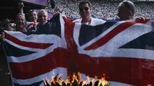 Fans are shown holding a Union flag, commonly known as a Union Jack,on a screen behind the Olympic flame during the London 2012 Olympic Games at the Olympic Stadium August 3, 2012. REUTERS/Eddie Keogh (Eddie Keogh/REUTERS)
