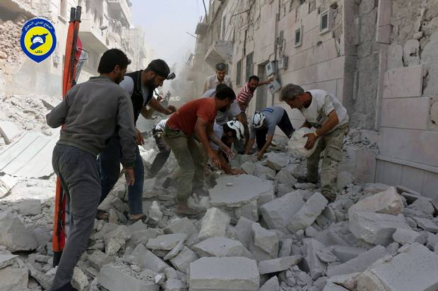 In this photo provided by the Syrian Civil Defense White Helmets, rescue workers work the site of airstrikes in the al-Sakhour neighborhood of the rebel-held part of eastern Aleppo on Sept. 21, 2016.
