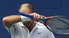Andre Agassi of the United States wipes his brow after falling behind Arnaud Clement of France during their singles match in the U.S. Open tennis tournament in New York Thursday, Aug. 31, 2000. (AMY SANCETTA)