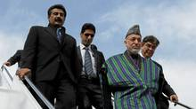 Afghanistan's President Hamid Karzai is escorted by Afghan officials as he walks down from his plane at a military base in Rawalpindi Feb. 16, 2012. (MIAN KHURSHEED/REUTERS/MIAN KHURSHEED/REUTERS)