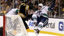 Adam McQuaid of the Boston Bruins checks Maxim Lapierre of the Vancouver Canucks during Game 6. (Elsa/2011 Getty Images)