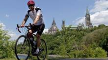 A cyclist rides with a helmet near Parliament Hill on July 8, 2010. Provincial governments should force anyone riding a bicycle to wear a helmet, says the co-author of a new report that found helmet use varies greatly across Canada. (Adrian Wyld/Canadian Press)