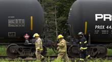 Firefighters in Nantes, Que., inspect a row of none oil tankers sitting on a railway siding there on July 10, 2013. This is where the ill-fated train that crashed and burned in Lac-Mégantic originated. (PETER POWER/THE GLOBE AND MAIL)