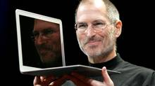 Steve Jobs holds up the new MacBook Air after giving the keynote address at the Apple MacWorld Conference in San Francisco on Jan. 15, 2008. (Jeff Chiu/AP)