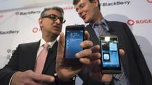 Research In Motion Ltd. President and CEO Thorsten Heins, right, and Rogers Communications Inc. President and CEO Nadir Mohamed show off their BlackBerry Z10 devices before presenting one to the first customer at a store in Toronto on Feb. 5, 2013. (Frank Gunn/The Canadian Press)