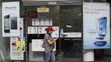 Advertising posters of Samsung Electronics' Galaxy S III, right, and Apple's iPhone 4S, left, are displayed at a mobile phone shop in Seoul, South Korea, Friday, Aug. 24, 2012. (Ahn Young-joon/AP)