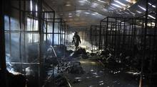 A firefighter inspects a burnt garment factory after a fire in the Bangladeshi town of Gazipur, 40 km (25 miles) north of Dhaka on October 9, 2013. (REUTERS)