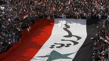 Pro-Syrian regime protesters carry a giant Syrian flag during a demonstration against the Arab League decision to suspend Syria, in Damascus, Syria, on Sunday Nov. 13, 2011. (Muzaffar Salman/The Associated Press/Muzaffar Salman/The Associated Press)