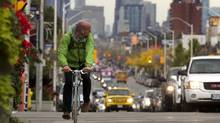 A cyclist pedals along in traffic on Danforth Ave. near Woodbine in Toronto on Oct. 21, 2013. A study presented at the annual conference of the Canadian Society for Exercise Physiology in Toronto in October suggested an increase of exercising benefits when pushing harder and breathing polluted air more deeply. (Peter Power/The Globe and Mail)