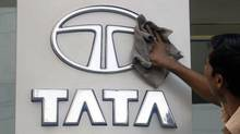 A worker cleans a Tata Motors logo outside its showroom in the southern Indian city of Hyderabad October 26, 2009. (KRISHNENDU HALDER/REUTERS)