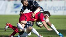 Team Canada's Hubert Buydens is tackled by Japan's Akihito Yamada, centre, and Michael Leitch during their international rugby match at Swangard Stadium in Burnaby, B.C., Saturday, June, 7, 2014. (Jonathan Hayward/The Canadian Press)