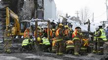 Emergency workers dig through the remains at the site of the Residence du Havre in L'Isle-Verte, Quebec, Jan. 28, 2014. (Mathieu Belanger/Reuters)
