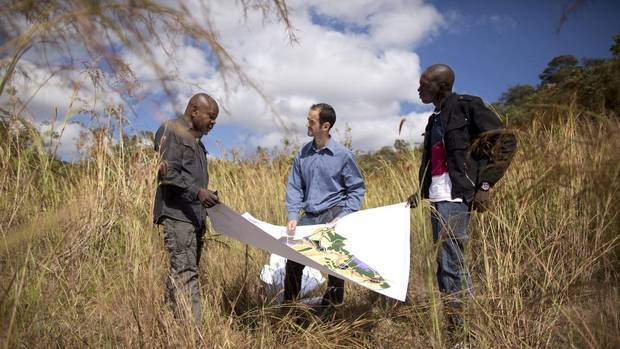 Mark Crandon of Russia's Renaissance Partners, centre, is standing with local employes Albert Mukomba, directeur general, left, and Yannick Kitambo, assistant de director, right, on the land where a large property development will be built outside Lubumbashi in the Democratic Republic of Congo. (John Lehmann/The Globe and Mail)
