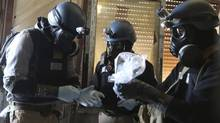 A United Nations chemical weapons expert, wearing a gas mask, holds a plastic bag containing samples from one of the sites of an alleged chemical weapons attack in the Ain Tarma neighbourhood of Damascus in this Aug. 29, 2013 file photo. (Reuters)