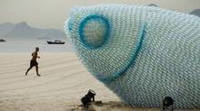 A man runs on Botafogo beach near a huge sculpture made from plastic bottles in Rio de Janeiro on June 19. The city is host to the United Nations Conference on Sustainable Development, which runs through June 22. (Victor R. Caivano/Associated Press)