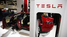 A Tesla model S car with an electric vehicle charging station is displayed during a media preview day at the Frankfurt Motor Show (IAA) in this file photo from September 10, 2013. Tesla Motors Inc reported November 5, 2013 a stronger-than-expected, third-quarter profit, but offered a fourth-quarter outlook that fell short of Wall Street estimates and the company's shares fell in after-market trading. (Kai Pfaffenbach/Reuters)
