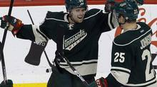 This Dec. 31, 2011 file photo shows Minnesota Wild left wing Pierre-Marc Bouchard, left, and right wing Nick Johnson (25) celebrating Bouchard's goal against the Phoenix Coyotes during the second period of an NHL hockey game in St Paul, Minn. The web site Ontheforecheck.com calculated how much each team will travel this NHL season and found the Minnesota Wild tops at 31,345 miles (49,890 kilometres). (Ann Heisenfelt/AP)