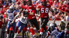 Calgary Stampeders' Simon Charbonneau-Campeau, centre, runs the ball during second half CFL football action against the Montreal Alouettes in Calgary on Saturday, June 28, 2014. (Jeff McIntosh/THE CANADIAN PRESS)