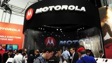 Participants are seen in a Motorola stand at the Mobile World Congress, the world's largest mobile phone trade show, in Barcelona, Spain, Monday, Feb. 27, 2012. (MANU FERNANDEZ/Manu Fernandez/AP)