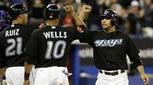 Alex Gonzalez celebrates RBI with Randy Ruiz and Vernon Wells of the Toronto Blue Jays against the Texas Rangers during a MLB game at the Rogers Centre May 15, 2010 in Toronto, Ontario, Canada. (Abelimages/Getty Images)